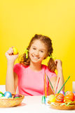 La fille de sourire s'assied à la table avec des oeufs de pâques Images stock