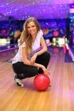 La fille de sourire s'assied avec la bille dans le club de bowling Images libres de droits