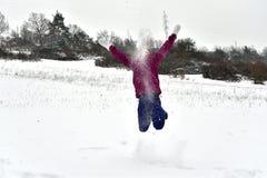 La fille de sourire saute et tombe dans la neige images libres de droits