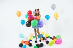 La fille de sourire semble heureuse tenant le groupe de grands ballons photos libres de droits