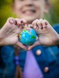 La fille de sourire tenant le globe dans des mains s'est pliée dans la forme du coeur Image stock