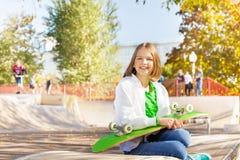 La fille de sourire tient la planche à roulettes, se repose dans le terrain de jeu Photo libre de droits