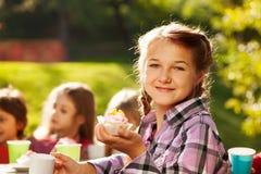 La fille de sourire tient le petit gâteau avec ses amis derrière Image stock