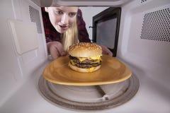 La fille de sourire tient le plat avec un hamburger dans des mains Mis dans la micro-onde sur la plaque tournante images libres de droits