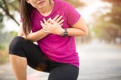La fille de sport ont la douleur thoracique après avoir pulsé ou en courant établissez en parc Concept de sport et de soins de sa photographie stock