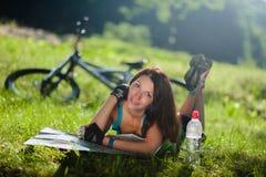 La fille de sport s'étendent sur une herbe avec une carte près de la bicyclette Image stock