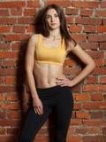 La fille de sport se tient près du mur Photo libre de droits