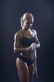 La fille de sport tournoie vers le haut de la ceinture sur des mains Image stock