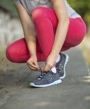 La fille de sports attache les dentelles sur des espadrilles, dehors Photographie stock libre de droits