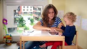 La fille de téléphone d'appel de mère et d'enfant d'aide jouent avec le comprimé banque de vidéos