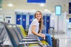 La fille de touristes avec le sac à dos et continuent le bagage dans l'aéroport international, attendant le vol Photographie stock