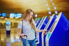 La fille de touristes avec le sac à dos et continuent le bagage dans l'aéroport international, faisant l'enregistrement auto- Photographie stock libre de droits