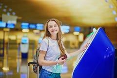 La fille de touristes avec le sac à dos et continuent le bagage dans l'aéroport international, faisant l'enregistrement auto- Photo stock