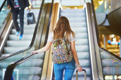 La fille de touristes avec le sac à dos et continuent le bagage dans l'aéroport international, sur l'escalator Photos libres de droits