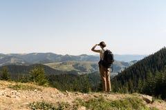 La fille de touristes de jeune randonneur tient le dessus de la montagne et regarde des collines avec des forêts et des prés Photos stock