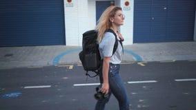 La fille de touristes marche avec l'appareil-photo banque de vidéos