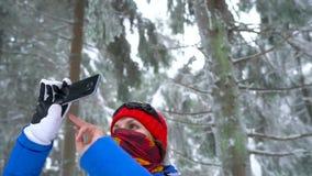 La fille de touristes seule marchant sur une forêt conifére couverte de neige d'hiver dans les montagnes et prend une photo de na clips vidéos