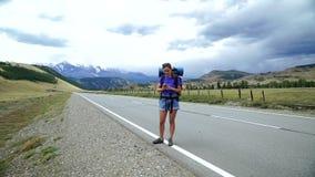 La fille de voyageur avec un sac à dos et des lunettes de soleil essaye d'attraper le signal de téléphone sur une route de montag banque de vidéos