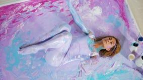 La fille de yoga se situe sur elle de retour dans la peinture sur la photo banque de vidéos