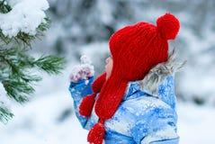 La fille dedans en rouge a tricoté le chapeau, les mitaines et la veste bleue marchant dans t Image stock