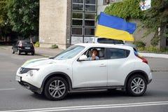 La fille derrière la roue d'une voiture, à laquelle un drapeau ukrainien Image stock