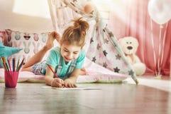 La fille dessine avec les crayons colorés images stock