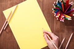 La fille dessine avec les crayons colorés sur le papier jaune sur la table en bois Maquette Image stock