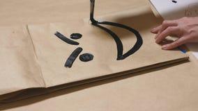La fille dessine avec une brosse sur de diverses émotions de sacs en papier Le concept des émotions dans les smiley photo stock
