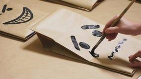 La fille dessine avec une brosse sur de diverses émotions de sacs en papier Le concept des émotions dans les smiley images stock
