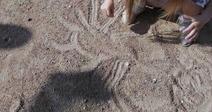 La fille dessine dans le sable clips vidéos