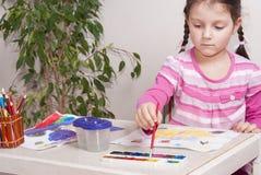 La fille dessine des peintures photographie stock libre de droits