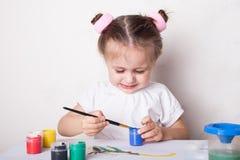 La fille dessine en peintures de couleur images stock