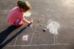 La fille dessine la craie de maison du soleil de peinture sur l'asphalte Photographie stock libre de droits