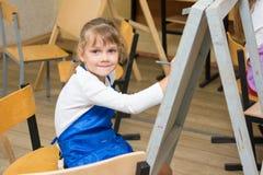 La fille dessine le crayon sur un chevalet pour dessiner une leçon et examiné le cadre Image libre de droits