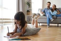 La fille dessine le mensonge sur les parents chauds de plancher s'asseyant sur le divan image stock