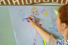 La fille dessine le stylo feutre sur le conseil photos stock