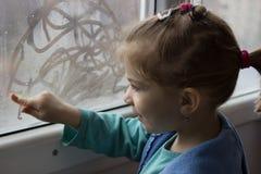 La fille dessine un doigt sur le verre photographie stock