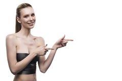 La fille dirige un doigt à l'espace vide du côté droit sur un blanc Image libre de droits