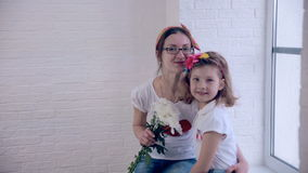 La fille donne à maman le bouquet des fleurs banque de vidéos