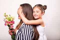 La fille donne des fleurs à sa mère son jour du ` s de mère image stock