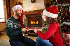 La fille donne le cadeau de Noël à l'ami Photo libre de droits