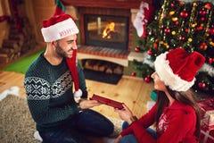 La fille donne le cadeau de Noël à son ami Photos libres de droits
