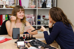 La fille donne le résultat des consultations sur l'artiste de makeupa Photographie stock libre de droits