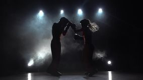 La fille donne un coup de pied le type qu'ils sont boxe d'entraînement pour kickboxing Fumez le fond Silhouette Mouvement lent clips vidéos