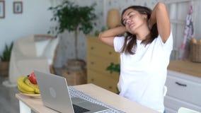 La fille dort à la table, se réveille et commence à travailler sur l'ordinateur portable, mouvement lent banque de vidéos