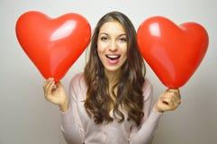 La fille douce avec le coeur de Valentine monte en ballon regardant l'appareil-photo Belle jeune femme avec deux ballons en forme Photo libre de droits