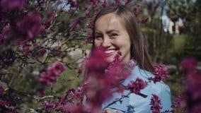 La fille douce dans un imperméable bleu se tient près d'un arbre fleurissant rose et sourit heureusement clips vidéos