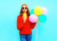 La fille drôle avec des ballons à air tient la tasse de jus de fruit sur le bleu Photographie stock