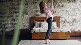 La fille drôle est dansante et chantante tenant le sèche-cheveux ayant l'amusement dans la chambre à coucher sur le tapis près du banque de vidéos