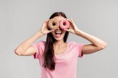 La fille drôle habillée dans le T-shirt rose tient deux butées toriques appétissantes lumineuses près de ses yeux comme des verre images stock